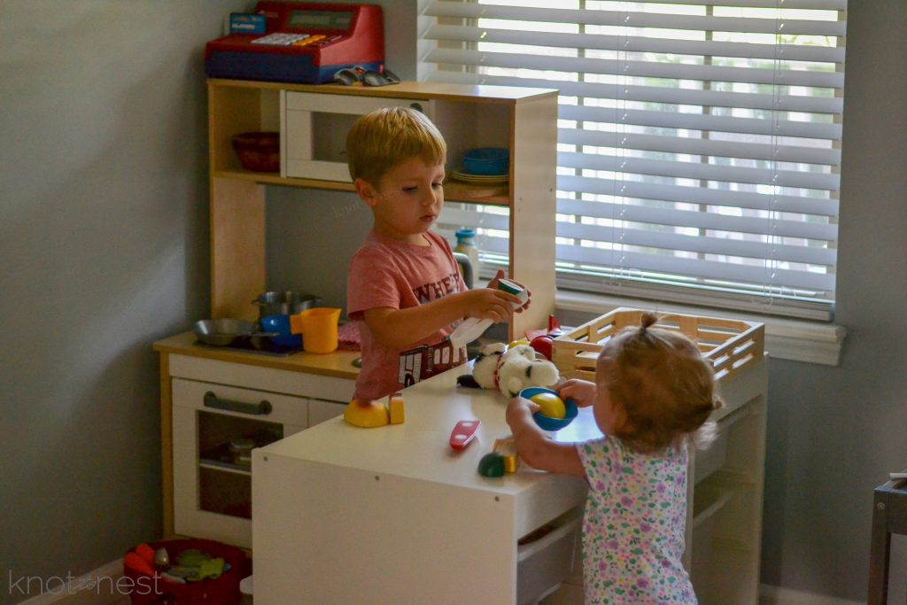 small boy and girl playing at their pretend kitchen
