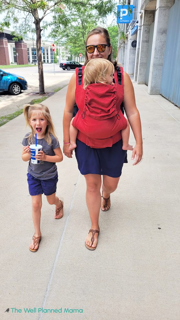 Mom walking with baby in carrier and young daughter next to her. busy mom new routines